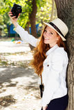 Nice girl photographer at work. Pretty red-haired girl with freckles on her face taking selfe in autumn park with camera Stock Photo