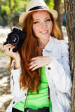 Nice girl photographer at work. Pretty red-haired girl with freckles on her face wearing hat walking in autumn park with camera Stock Image