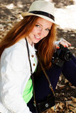 Nice girl photographer at work. Pretty red-haired smiling girl photographer at work Stock Photo