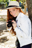 Nice girl photographer at work. Pretty smiling girl with camera is walking in autumn park Stock Photos