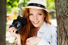 Nice girl photographer at work. Pretty smiling red-haired girl with freckles on her face walking in autumn park with camera Stock Photography