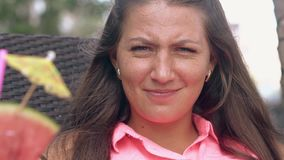 Nice girl in pink blouse makes angry face and smiles. Nice girl in pink blouse makes angry face and poses smiling on lounge chair and sweet cocktail in hands stock footage
