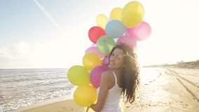 Nice girl playing with balloons on the beach. Girl having fun on the beach with balloons