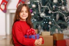 Nice girl playing near Christmas tree Royalty Free Stock Image