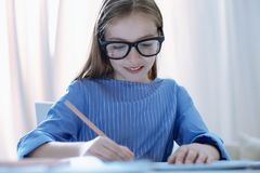 Nice girl with poor eyesight doing homework Stock Photos