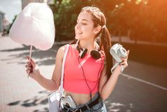 Nice girl is posing. She is holding cotton candy in one hand and camera in the other one. Also there is headphones. Around her neck and music player in pant Stock Photos