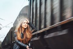 Nice girl on a railway road near moving train. Nice girl in a black dress on a railway road near moving train Stock Image