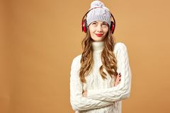 Nice girl in red headphones dressed in white knitted sweater and hat stands on a beige background in the studio.  stock photos