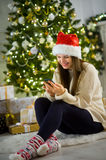 Nice girl in Santa`s cap sits near Christmas tree with mobile phone in hands. Stock Photo