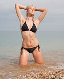 Nice girl at the sea. Attractive young long-haired blond woman in black swimsuit at the sea Stock Image