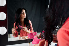 Nice girl shows long hair near the mirror Royalty Free Stock Photo