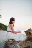 A nice girl sits on the sea shore Stock Images