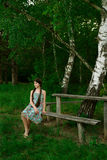 Nice girl sitting in the forest on the wooden bench Royalty Free Stock Photography