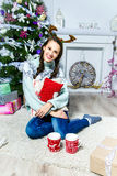 Nice girl sitting near the Christmas tree in a white room Stock Photos