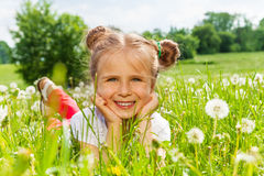 Nice girl smiles laying on a grass Royalty Free Stock Image