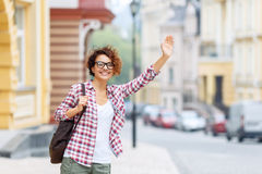 Nice girl standing in the street. Hey you. Pretty cheerful smiling girl holding her bag and rising her hand while standing in the street Stock Photo