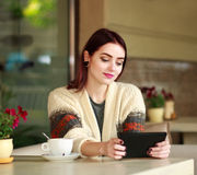 Nice girl in summer cafe looking at tablet Stock Photos