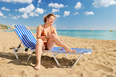 Nice girl with sun-protection cream. On beach stock images