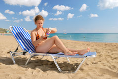 Nice girl with sun-protection cream. On beach royalty free stock images