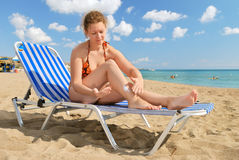 Nice girl with sun-protection cream. On beach stock photos