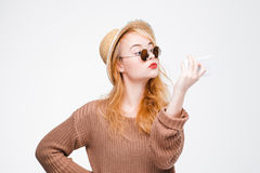 Nice girl in sunglasses taking selfie with mobile. Nice young woman in straw hat and sunglasses taking selfie with mobile phone. Cool and fashionable hipster Royalty Free Stock Photo