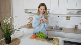 Charming woman cooks phone in hands and composes composition of. Nice girl takes photo on mobile and displays two cucumbers, red tomato and leaves of green salad Royalty Free Stock Photos