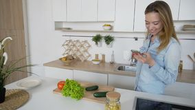 Charming woman cooks phone in hands and composes composition of. Nice girl takes photo on mobile and displays two cucumbers, red tomato and leaves of green salad Stock Images