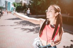 Nice girl is taking selfie. She is looking at camera and smiling. Also she is holding a piece of her hair in hands. Girl. Is posing Stock Photography
