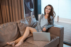 Nice girl using laptop sitting in the room Stock Image