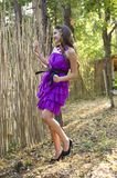 Nice girl in violet dress near wicker fence Royalty Free Stock Photography