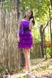 Nice girl in violet dress near wicker fence Royalty Free Stock Photo