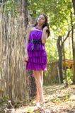 Nice girl in violet dress near wicker fence Royalty Free Stock Photo
