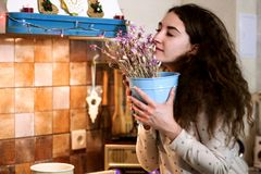 Nice girl smells at flowers. Nice girl wearing pijama smells at flowers in the kitchen royalty free stock photography
