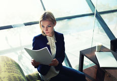 Nice girl in a white blouse studies report before departure. Portrait of young blond hair business woman reading documents in bight light office interior sitting stock photo