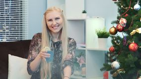 Nice girl is wishing `Happy New Year` with a glass of drink. Nice girl is wishing Happy New Year with glass of drink. She sits near the Christmas tree at the New stock video