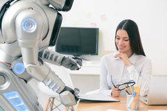 Nice girl working with robot in the office Royalty Free Stock Photography