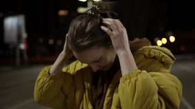 A nice girl in a yellow soft jacket stands in the middle of a dark street and gathers her hair in a bun.  stock footage