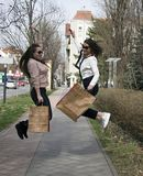 Black Friday sale - holiday shopping concept 2019.. Nice girls jump out of luck after shopping.With bags in your hands royalty free stock images