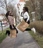 Black Friday sale - holiday shopping concept 2019. Nice girls jump out of luck after shopping.With bags in your hands. n stock photos