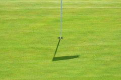 Nice golf course on a sunny summer day. Hole with a flag. Popular outdoor sport. Stock Photography