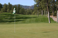 Nice golf shot with ball close. Shot of a golf ball close to the pin on a beautiful course in the mountains Stock Photography