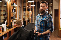 Nice good looking barber holding a comb Stock Photography