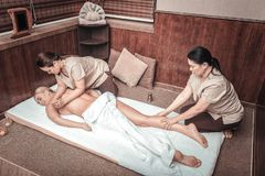 Nice good looking woman visiting a spa center. Small pleasures. Nice good looking women having a massage while visiting a spa center royalty free stock photography