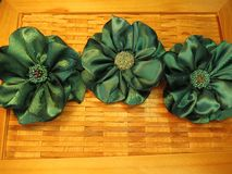 Beautiful fabric flowers - brooch on wooden surface Royalty Free Stock Images