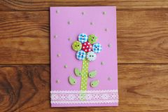 Nice greeting card isolated on a wooden background. Greeting paper card for happy birthday or mother`s day or father`s day. Paper craft for kids with folding stock image