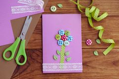 Nice greeting card made by a kid for mothers day, fathers day, March 8, birthday. Handmade card with a flower from wooden buttons. Mothers day cards to make in royalty free stock image