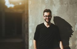 Nice guy in glasses and with beard. Portrait of the young smiling bearded man with the neat haircut and in glasses, standing near the concrete wall with strong Stock Photos