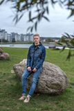 Nice guy in jeans jacket sits on a stone in the park in a nightfall Royalty Free Stock Images