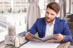 Nice guy reading price list in cafe. What a variety. Portrait of young handsome man with beard sitting in cafe and looking through menu stock photography