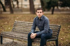 Nice guy sitting on the bench outdoors in cloudy weather.  Royalty Free Stock Image